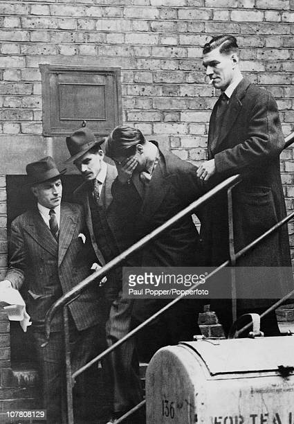 17yearold Terence Peter Holt covers his face as detectives escort him away after his hearing at Great Marlborough Street Magistrate's Court London...