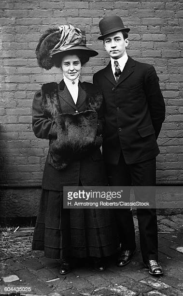 1800s 1890s TURN OF THE 20TH CENTURY COUPLE STYLISH FASHIONABLE CLOTHES MAN IN BOWLER HAT WOMAN IN PLUMED HAT LOOKING AT CAMERA
