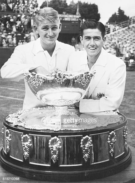 Melbourne, New Zealand: Justifiably satisfied with themselves, Lewis Hoad and Ken Rosewall stand behind the Davis Tennis Cup, which they successfully...