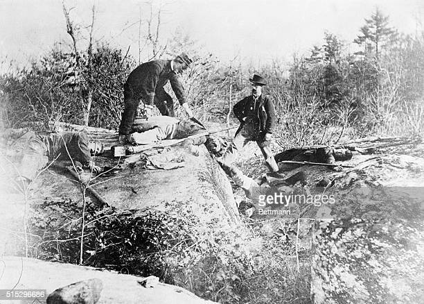 Gettysburg, PA: Civil War- The Battle of Gettysburg. Devil's Den shows men looking over Union dead on the ground after the battle. Photograph.