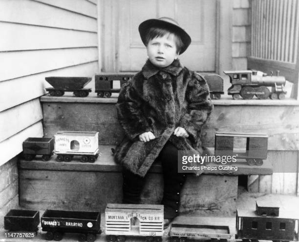 1880s 1890s 1900s BOY WEARING FUR COAT SITTING ON STEPS SURROUNDED BY TOY RAILROAD TRAINS LOOKING AT CAMERA