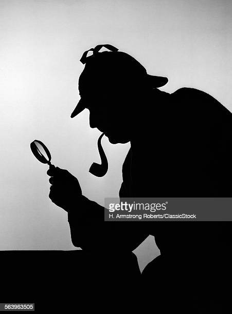 1880s 1890s SILHOUETTE OF CONSULTING DETECTIVE SHERLOCK HOLMES SMOKING A PIPE HOLDING MAGNIFYING GLASS AND LOOKING FOR CLUES