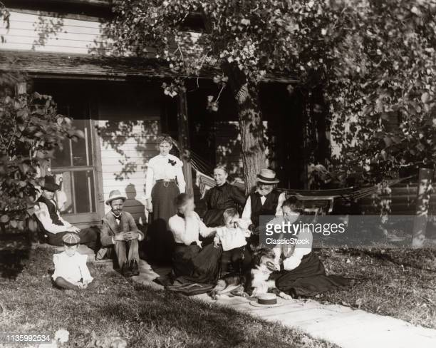 1890s 1900s TURN OF 20TH CENTURY THREE GENERATIONS OF EXTENDED FAMILY A DOG SITTING ON LAWN OF HOUSE ON A SUMMER DAY