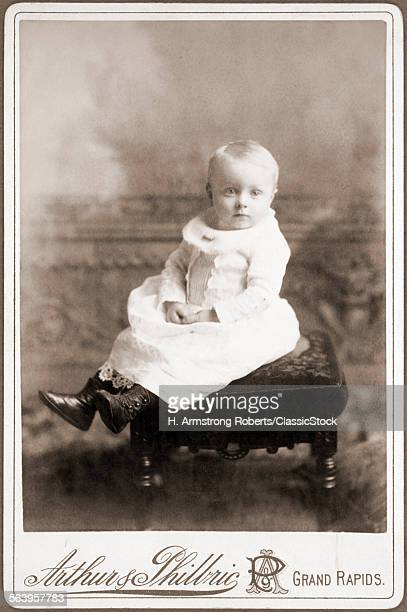 1890s FORMAL STUDIO PORTRAIT OF BABY IN HIGH BUTTONED SHOES AND LONG DRESS SITTING ON STOOL