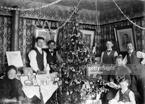 1890s TURN OF 20th CENTURY GROUP PORTRAIT FAMILY THREE GENERATIONS LOOKING AT CAMERA POSING BY CHRISTMAS TREE GIFTS