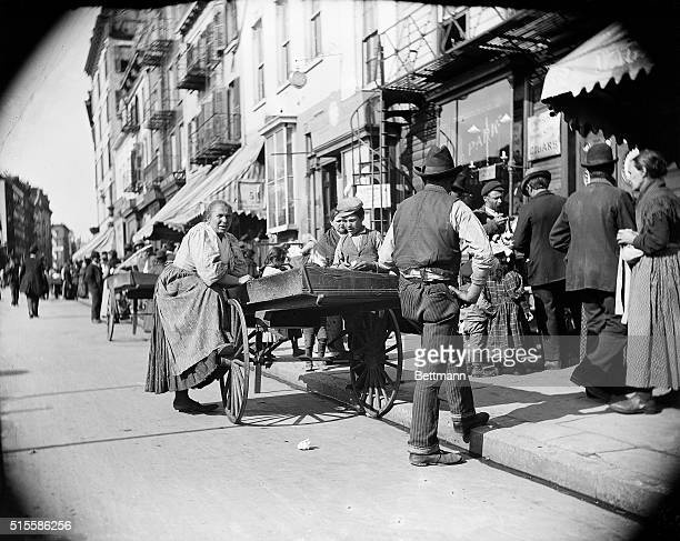 Photo shows pushcart peddlers at Mulberry Street waiting for trade.