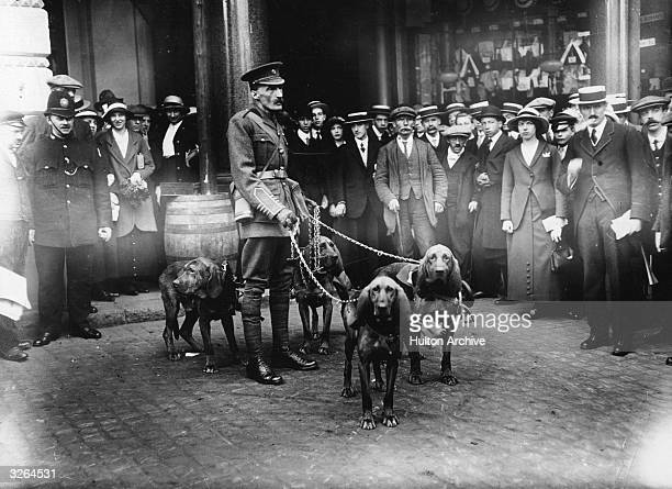 A crowd of onlookers watches Major Richardson with his bloodhounds at Charing Cross They are going to assist the British Red Cross in locating...