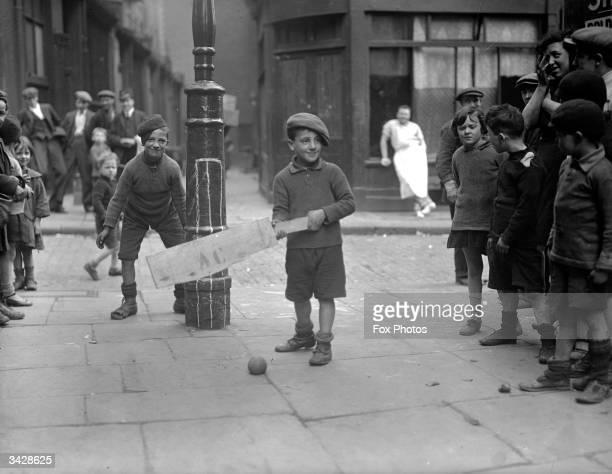 Boys play cricket in the street