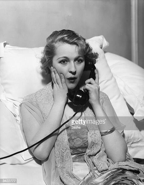 Actress Margaret Bannerman gets a surprising phonecall in a scene from the film 'Gay Love'