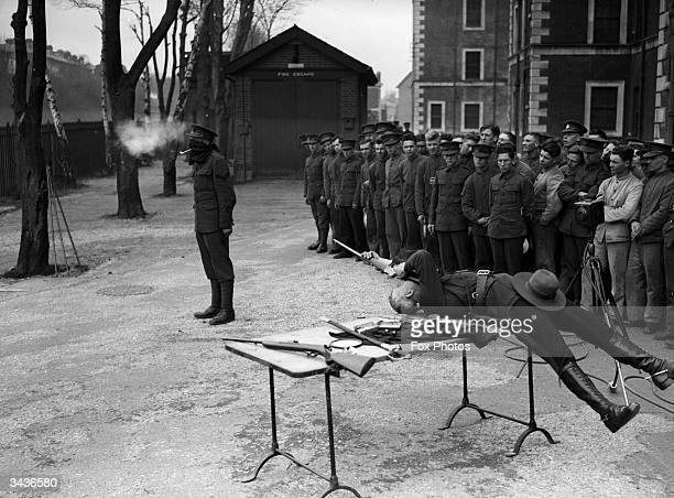 Captain George Ash lies on his back as he prepares to shoot the bowl from the clay pipe held between a blindfolded corporal's teeth