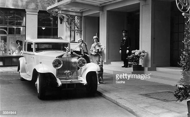 Mrs Ivor Bauch and Mrs Evan Morgan along with their German Shepherd dog arrive in their Rolls Royce motor car at The Grosvenor House Hotel in London