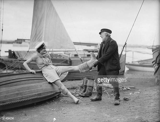 William Kent an 89 year old boatman from Benfleet Essex helping a young sailor girl off with her boots