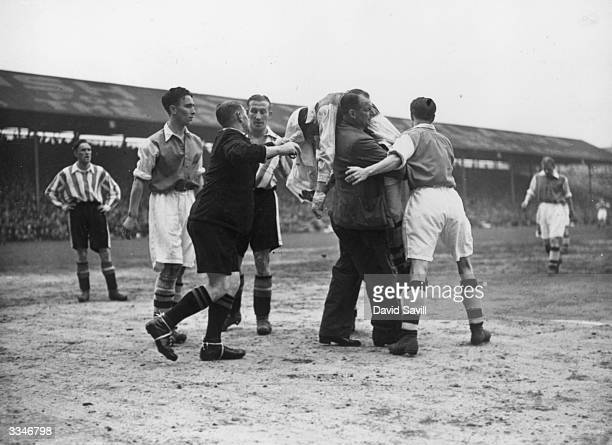 Ted Drake, the Arsenal centre-forward, is carried off the field by the Arsenal trainer after being knocked unconscious during a match between...