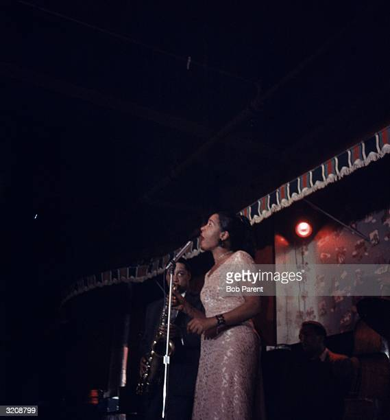 American jazz singer Billie Holiday performs on stage backed by a saxophonist and a drummer at the Sugar Hill nightclub Newark New Jersey