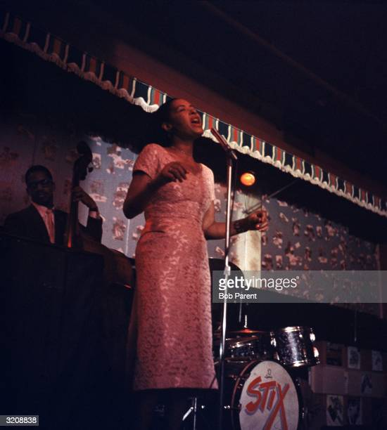 American jazz singer Billie Holiday sings on stage accompanied by a drummer and an upright bass player at the Sugar Hill nightclub Newark New Jersey
