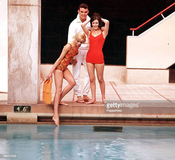 18th April 1964 Swimwear A man wearing a white robe stands with two attractive young women in their swimsuits by the side of a pool as the blonde...