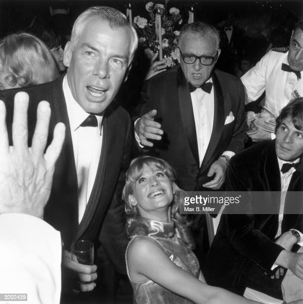 American actor Lee Marvin holding a drink speaks while British actor Julie Christie looks up and smiles from a table during a party for the Academy...