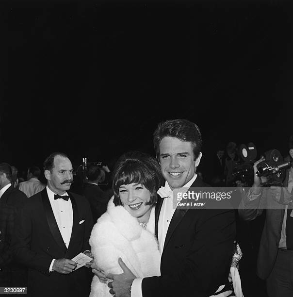 EXCLUSIVE American actors and siblings Warren Beatty and Shirley MacLaine embrace as cameramen and guests crowd behind them at the Academy Awards...