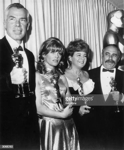 Four Oscar winners holding their statuettes after the ceremony at the Civic Auditorium Santa Monica From l to r Lee Marvin Julie Christie Shelley...