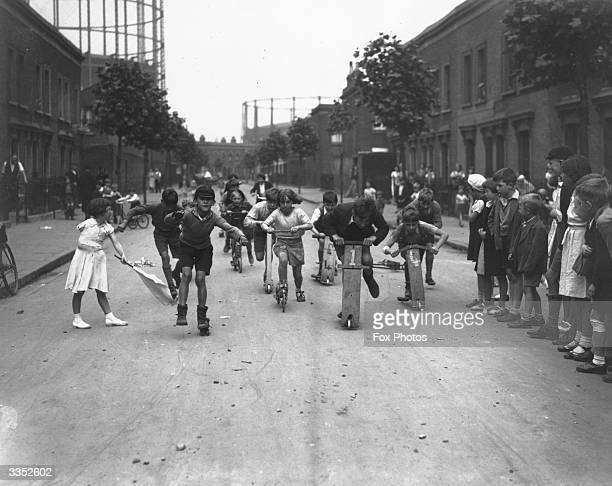 Children racing scooters in a street in Poplar E14 London