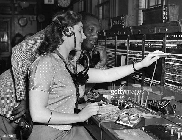 West Indian cricketer Prior Jones being shown how a switchboard works during his team's visit to a telephone exchange.
