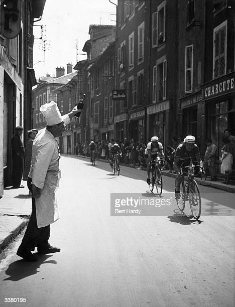 A chef cheers on participants in the 1951 Tour de France as they speed past his restaurant Original Publication Picture Post 5381 The Greatest Show...