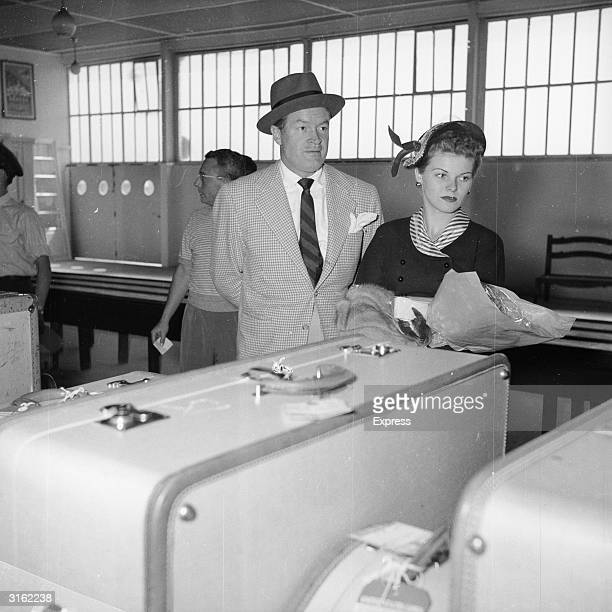 British-born American comedian Bob Hope and his singer Betsy Duncan collect their luggage.