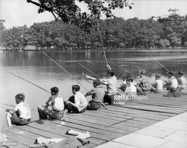 A group of children take part in a fishing competition at Grovelands Park Southgate during the school summer holidays One of them boasts a small catch