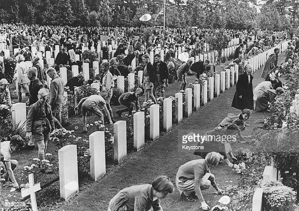 Children placing flowers on individual graves at the Airborne Forces' Cemetery at Oosterbeek near Arnhem, Holland, on the ninth anniversary of the...