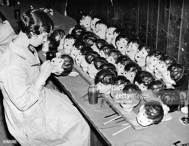 A worker painting celluloid dolls heads at a factory in Leicester