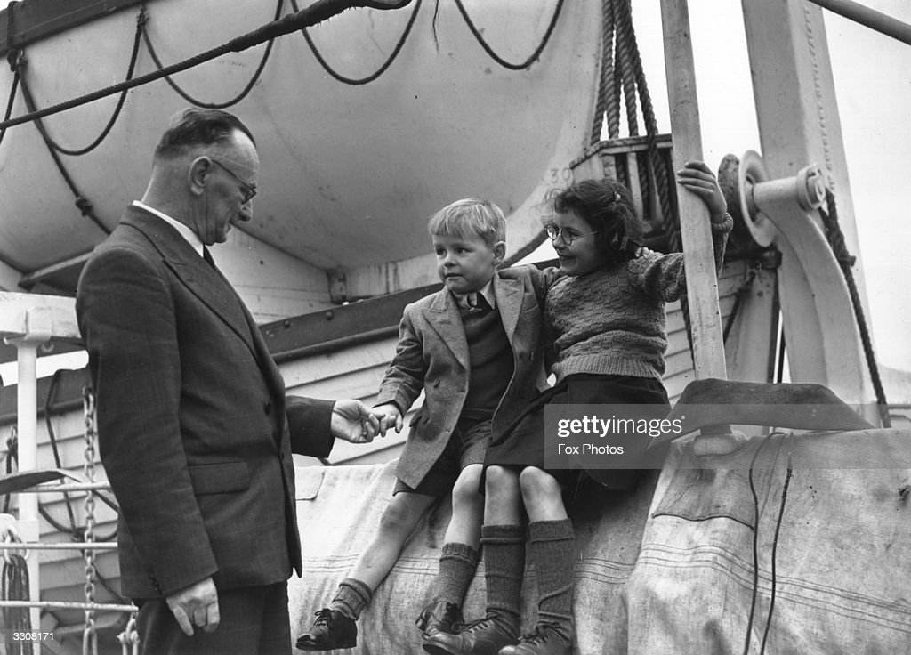 Mr Kitson, agent-general for Western Australia, talks to two young children who are about to emigrate from the Fairbridge Farm Schools in England to the Kingsley Fairbridge Farm Schools in Western Australia. They are aboard the liner 'Ormonde'.
