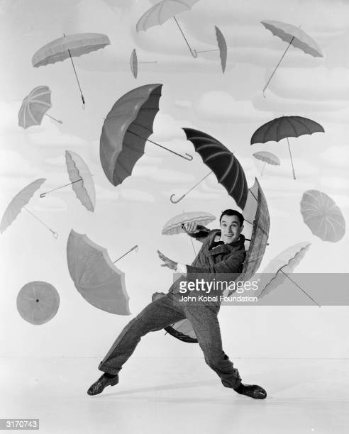 Gene Kelly the director and choreographer of the MGM musical 'Singing in the Rain' performs a dance routine surrounded by a collection of umbrellas