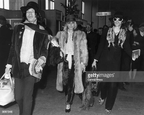 Rolling Stones lead singer Mick Jagger and the band's lead guitarist Keith Richards at London Airport with the German Actress Anita Pallenberg The...