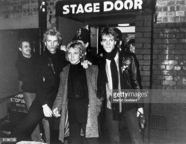 The pop group Police outside the stage door of a Hammersmith venue in west London with a policeman standing behind them From left to right they are...