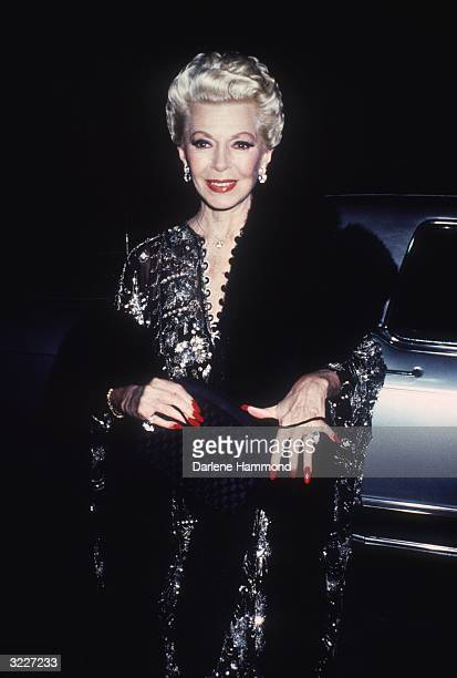 American actor Lana Turner with platinum blonde hair and red lips and nails smiles while arriving for a party for the TV show 'The Love Boat' aboard...