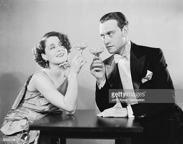 Canadian actress Norma Shearer shares a drink with a suspicious Conrad Nagel in the film 'The Divorcee' directed by Robert Z Leonard