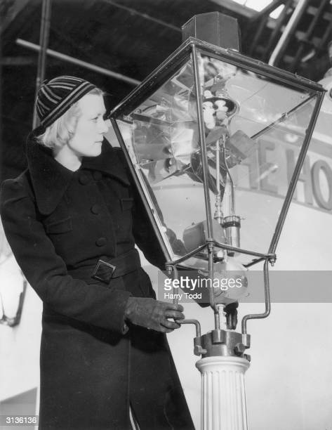 A visitor at the Castle Bromwich section of the British Industries Fair inspecting the Newbridge valve attachment on a street lamp which enables the...