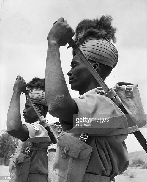 Two members of the Sudan Defence Force Infantry in feathered turbans show how they carry and draw their bayonets Their uniform includes feathered...