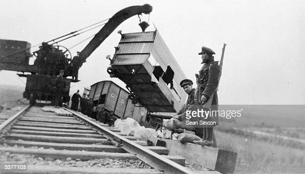 Soldiers look on as a crane lifts derailed train carriages back onto the tracks at Ardfert during the Irish Civil War