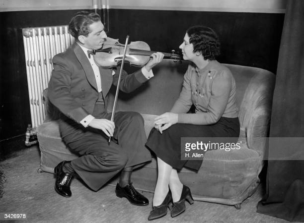 Annunzio Paolo Mantovani , the famous Tipica orchestra leader and violinist serenades his sister Stella Roberta, a singer with the orchestra, at the...