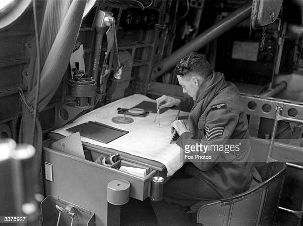An RAF sergeant at work with a compass and map plotting a route at the RAF's Coastal Command