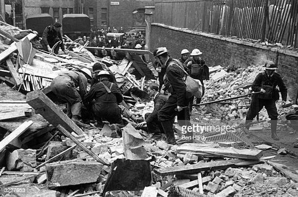 A stretcher party searches for casualties amongst the wreckage of a building during World War II Original Publication Picture Post 351 Rescue pub 1941