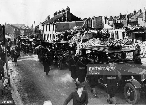 Funeral cars drive slowly through a bomb-damaged street in Portsmouth, accompanied by an escort of British soldiers and sailors. Twenty-five victims...