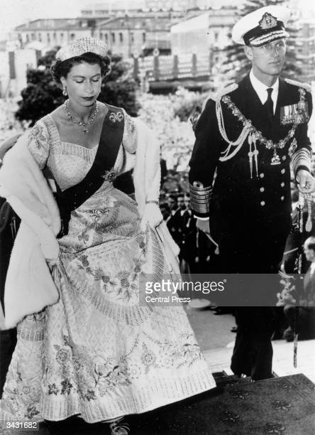 Queen Elizabeth II, wearing her Coronation dress, arriving with the Duke of Edinburgh to open Parliament in Wellington, New Zealand.