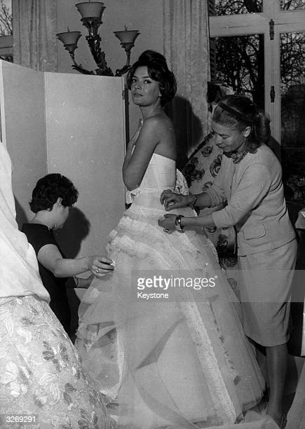 Mlle Carven, head of the Paris fashion house Carven, right, puts the finishing touches to one of her wedding dress designs during preparations for...