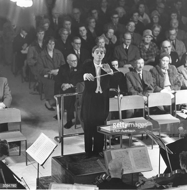 The English conductor and cellist Sir John Barbirolli , conducting the Halle Orchestra at Guildford Cathedral. He is the principal of the Halle...