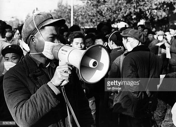 Members of the Red Guards in China their mouths masked against flu germs on the orders of Chairman Mao address the passing crowds as part of the...