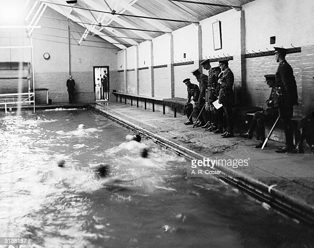 King George V watching swimmers in the pool on a visit to the Royal Military Academy Woolwich