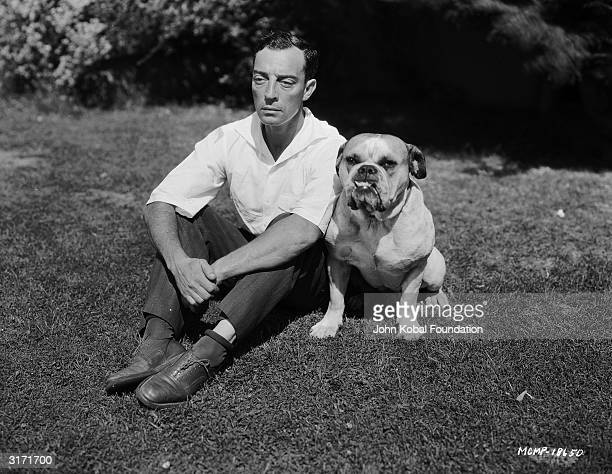 American silent screen comedian and actor Buster Keaton sits beside a bulldog