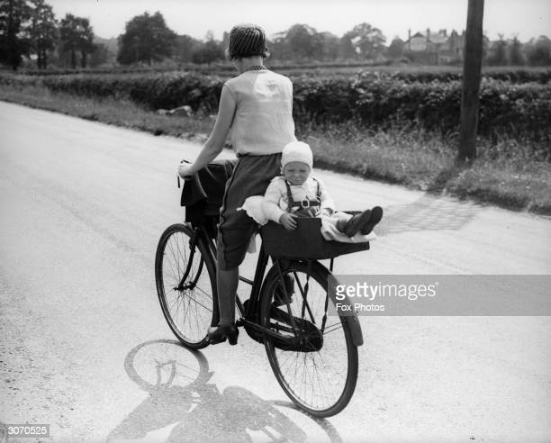 A mother cycles off with her young toddler on the passenger seat of her bicycle